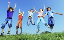 KIDS Jumping in Grass