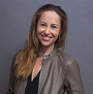 Smiling woman wearing taupe leather jacket with long blondish brown hair