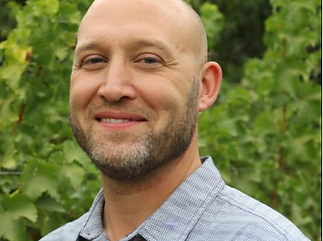 Smiling bald white man in front of trees