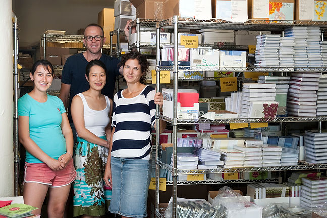 Interise 3 women and 1 man standing by shelves of school supplies and books
