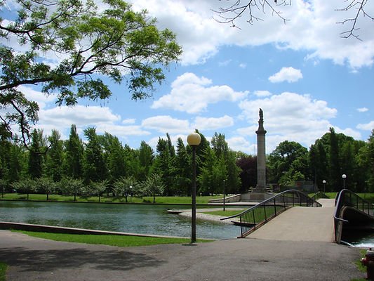 Allegheny Commons area with trees and stone monument