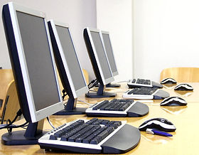 Four desktop PC computers with keyboards on wooden table