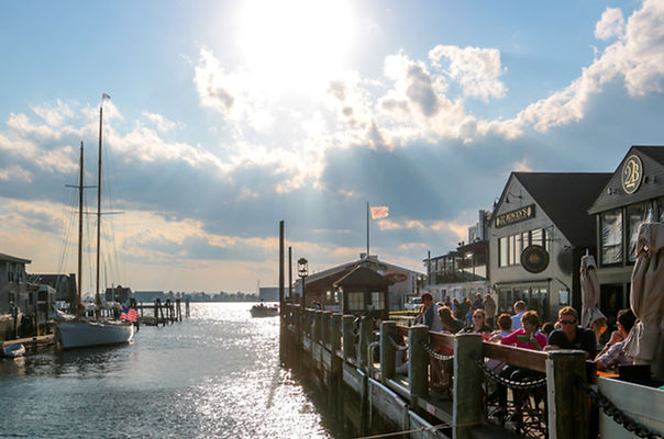 Newport Harbor with boat masts and outdoor restaurant seating at 22 Bowen's wine bar and grille