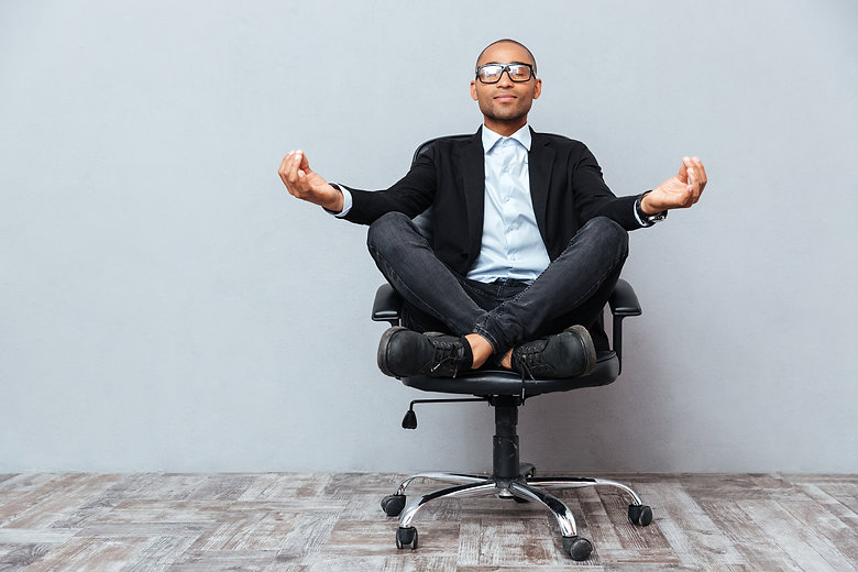Relaxed handsome african young man sitting and meditating on office chair.jpg