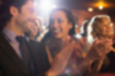 Close up of couple clapping in theater
