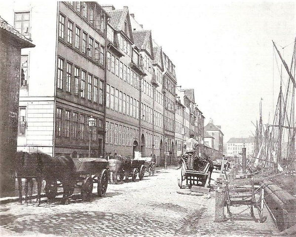Den 'pæne side' af Nyhavn fotograferet i 1865. Det var før Holbergsgade blev anlagt. Da hed den lille gade tv. Nær Nyhavn. Oppe ved Kongens Nytorv ses bygningerne fra Botanisk Have, der flyttede i 1871. Foto: Københavns Museum