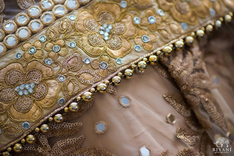 Picture of  Indian Bride's outfit with intricate embroidery, gold beads, and glass needs on a champagne toned fabric - Indian Wedding Coordinator