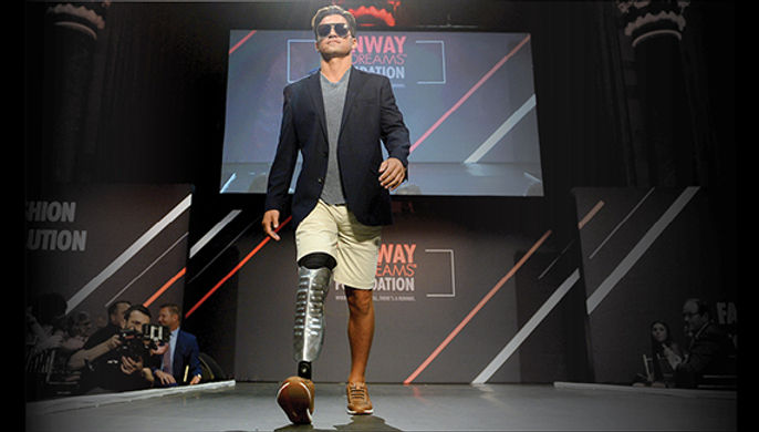Man on runway with artificial let in dress shorts, and sport coat