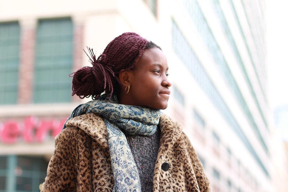 Photo of Jessica Felicity Kasiama in a leopard print coat with a scarf and her hair up in a bun