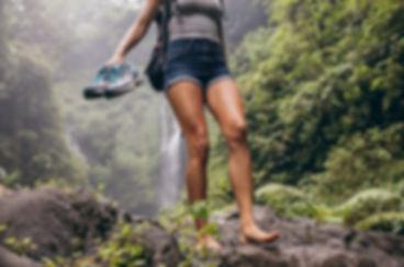 Femme qui randonne pieds nus devant une cascade ses chaussures à la main