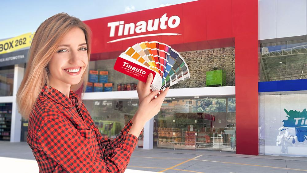 Mulher jovem segurando uma cartela de cores com loja de tinta Tinauto ao fundo.