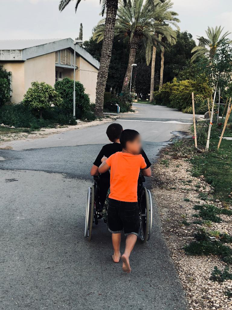 חניך בעמותת ״בית גלגלים״ בעל שיתוק מוחין ביחד עם ילד בן קיבוץ ניר דוד