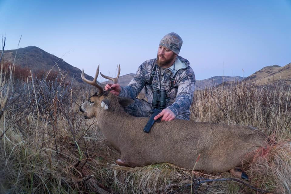 John admires his second sitka-blacktail buck, taken with a Kimber 10mm pistol.