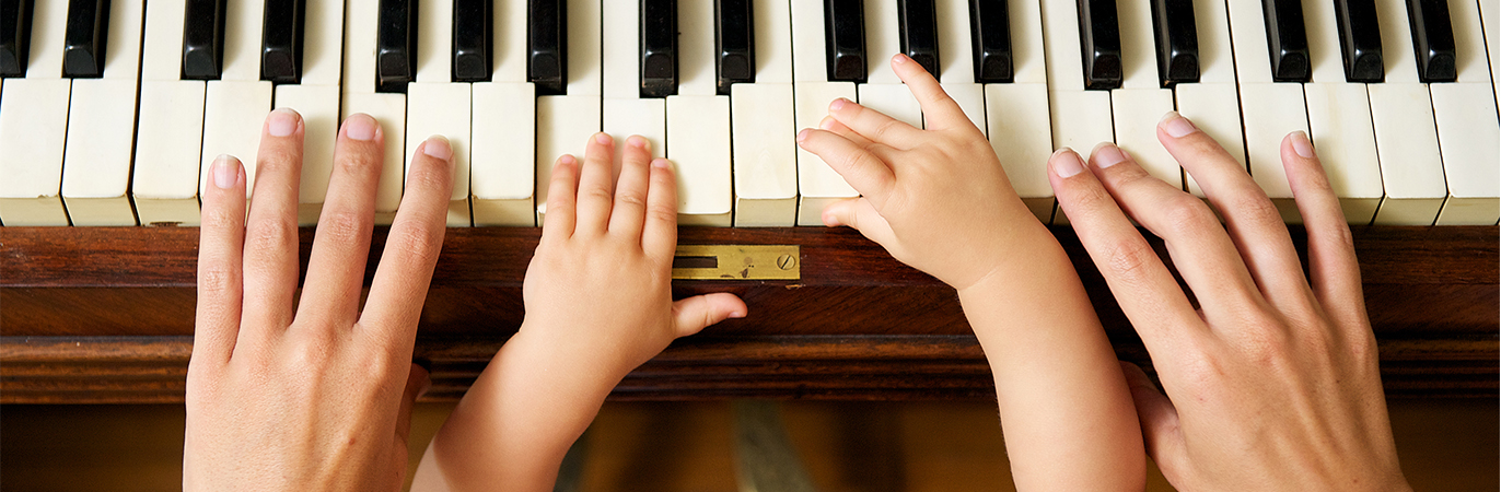 Student and teacher's hands on piano