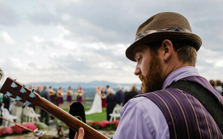 Chad Verbeck, local singer/ songwriter, plays guitar at a wedding