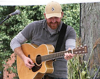 Chad Verbeck playing guitar at a local music festival