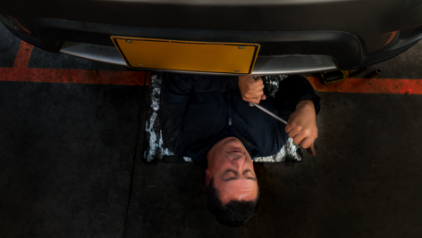OVERHEAD shot of a YOUNG MAN on a creeper seat, partially under a vintage hot rod. He wipes the sweat that's gathered along his unruly mustache, leaving a sooty mark, and reaches for his headlamp.  SFX: CLICK