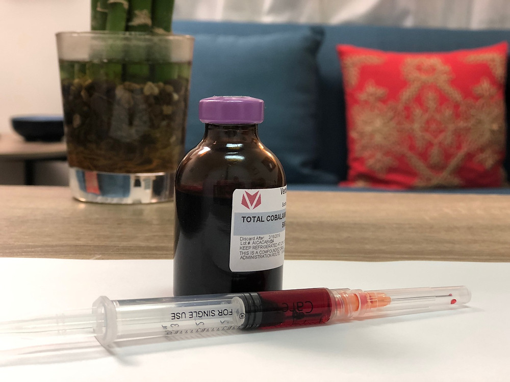 Bottle of B12 supplement with filled syringe ready to administer to a patient