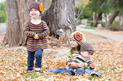 Adorable family of three (2 girls, 1 boy) in the leaves