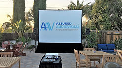 Photo of a large outdoor projection screen and speakers