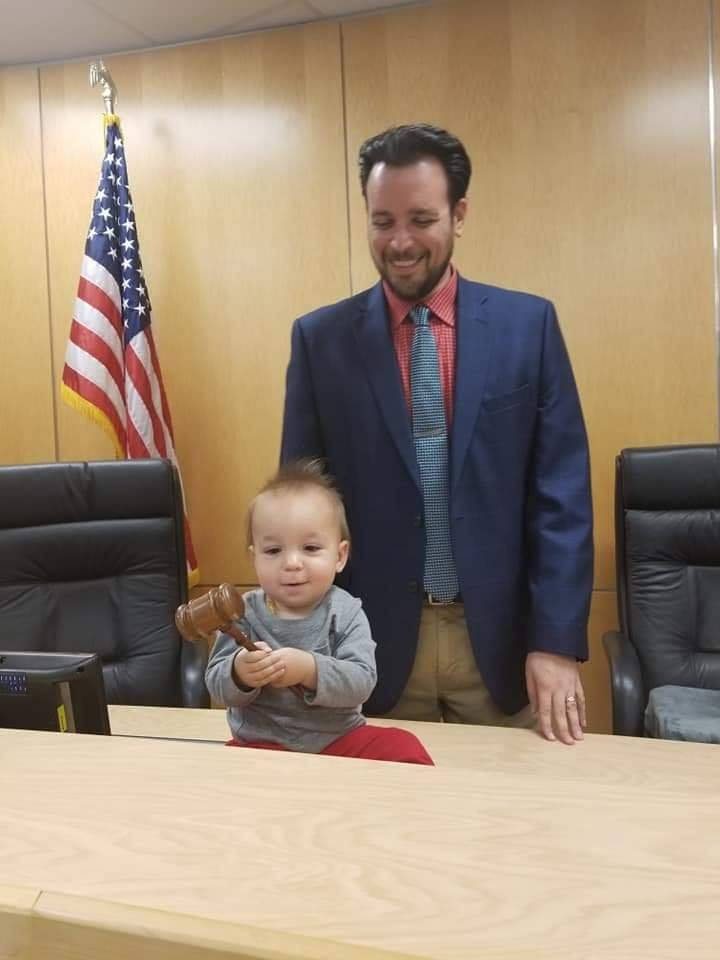 Jared enjoying a visit from his youngest son, Lorenzo on the city council dais.