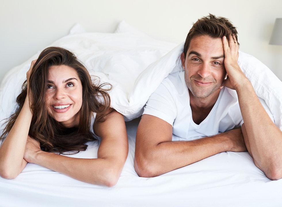 Happy_Couple_Lying_In_Bed.jpg