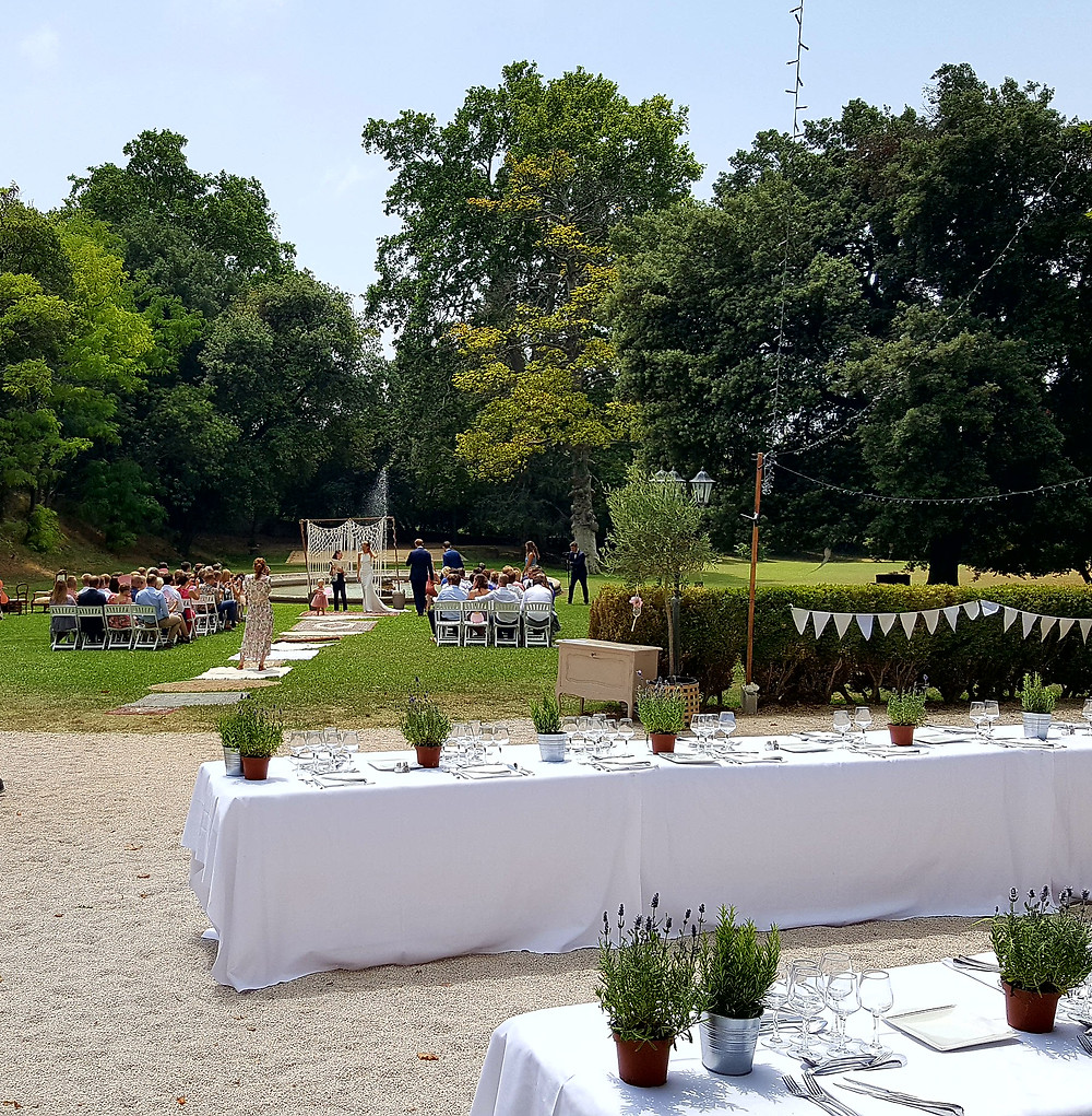 """Old rugs line the """"aisle"""" leading to the wedding arch, with tables set for the wedding banquet in the foreground"""