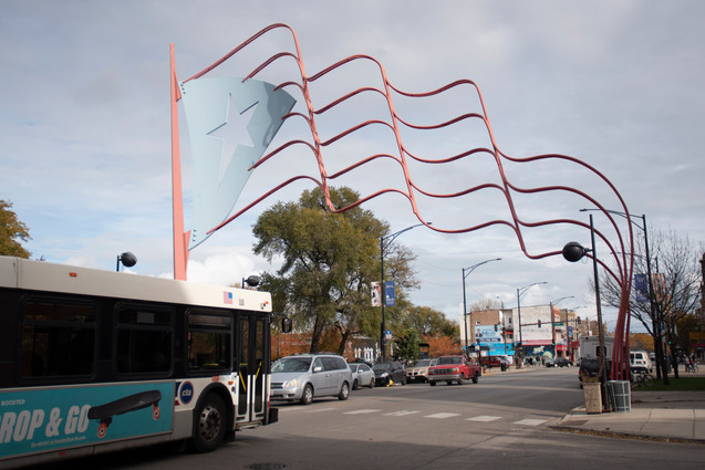 A bus travels eastbound underneath a sculpture of the Puerto Rican flag in the Humboldt Park neighborhood in Chicago. | Colin Boyle