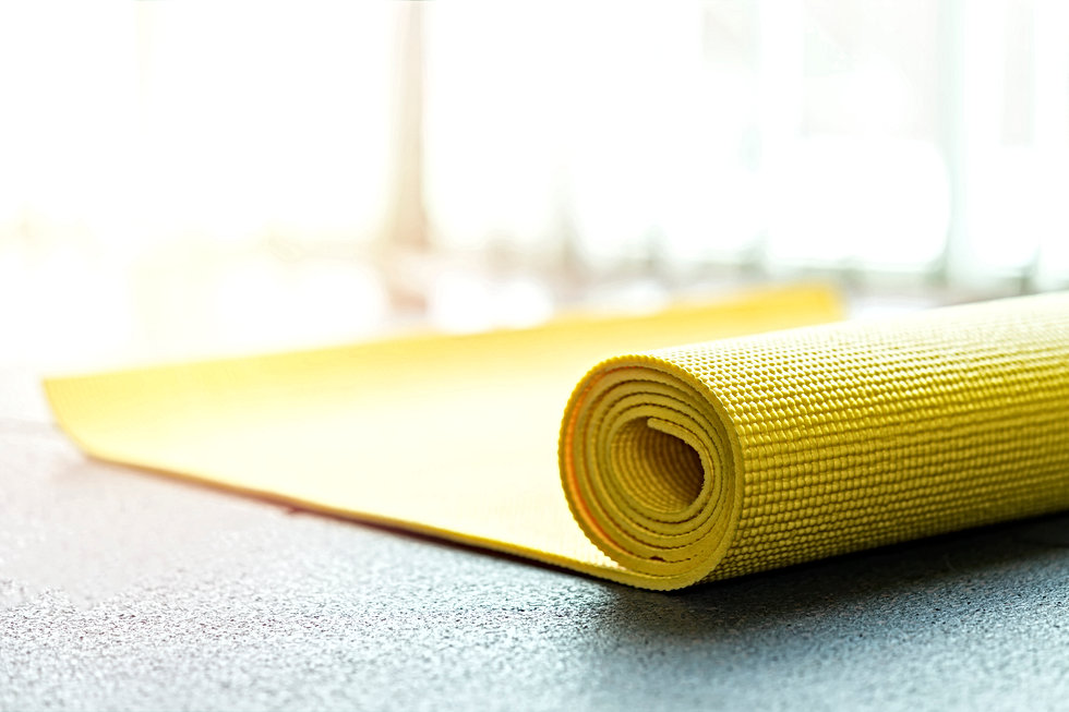 Yellow yoga mat on rubber floor in gym,