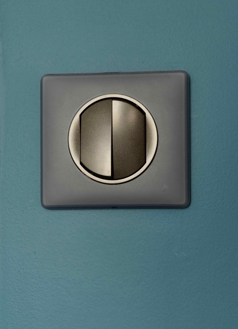 interrupteur gris sur murs bleus