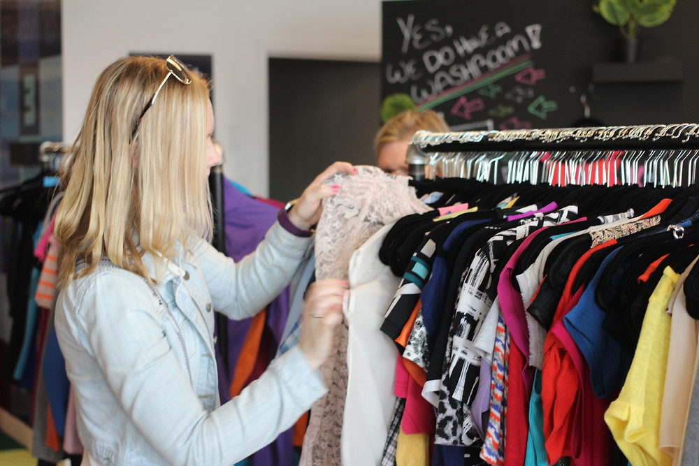 A young person can be seen pulling clothes from clothing racks at  Neighbourhood thrift store, a Choices for Youth social enterprise.