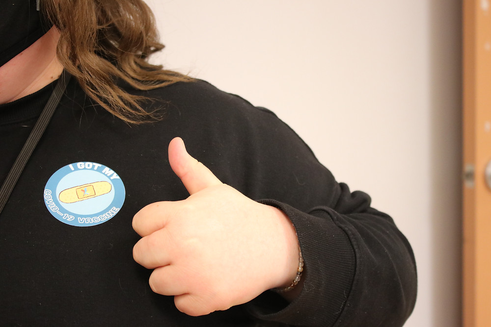 A person giving a thumbs up while wearing a ' I got my COVID-19 vaccine' sticker