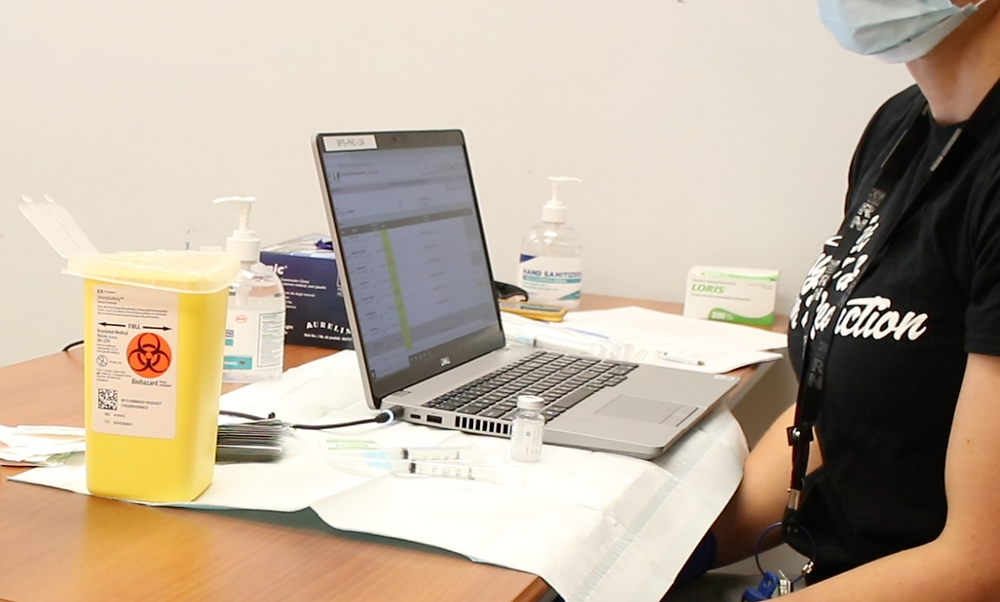 A nurse sits at a table with a laptop, and vaccine materials.
