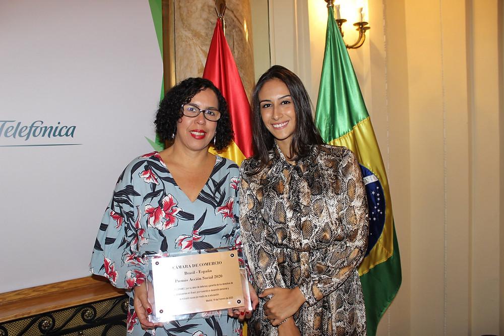 Adriana de Amorim (ACOPAMEC) segurando a placa do Prêmio ao lado da Laura Baie ( Instituto Neoenergia).