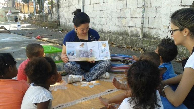 voluntária da FASC lendo livro para um grupo de crianças sentadas em círculo ao redor dela, em uma rua com um muro atrás