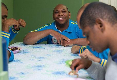 Acolhidos do Lar sorrindo durante uma de suas refeições