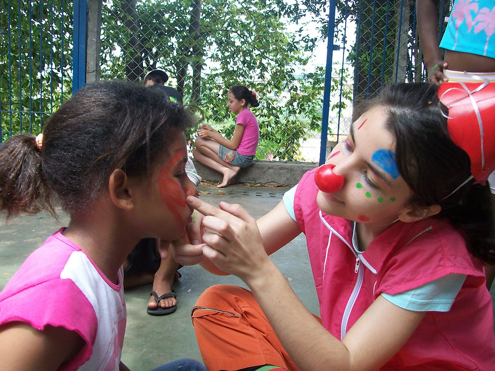 Voluntária com rosto pintado e usando nariz de palhaçopintando o rosto de uma criança durante uma festa de celebração
