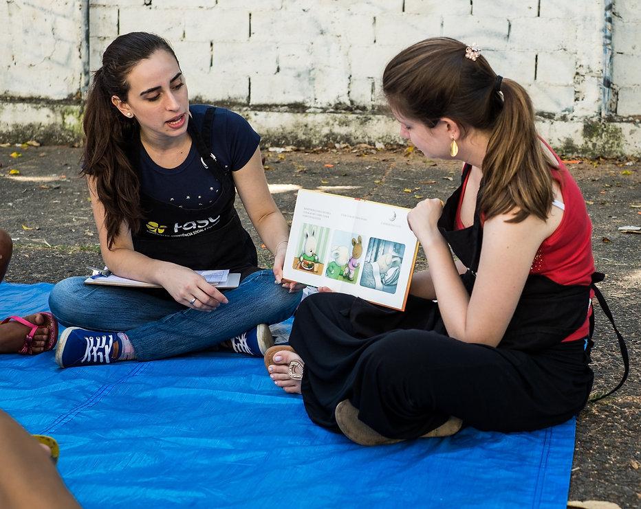 Voluntárias lendo um livro infantil para crianças.