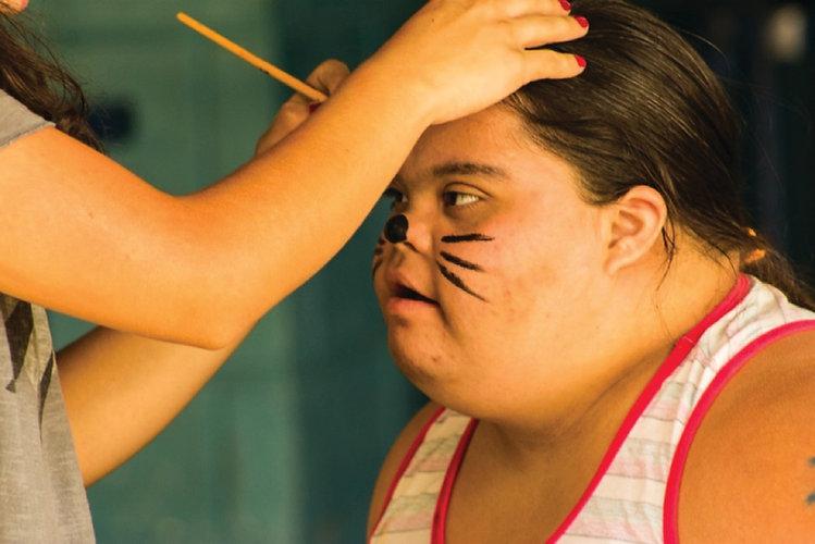 Menina com transtorno mental com o rosto pintado enquando conversa com um profissional do ILA.