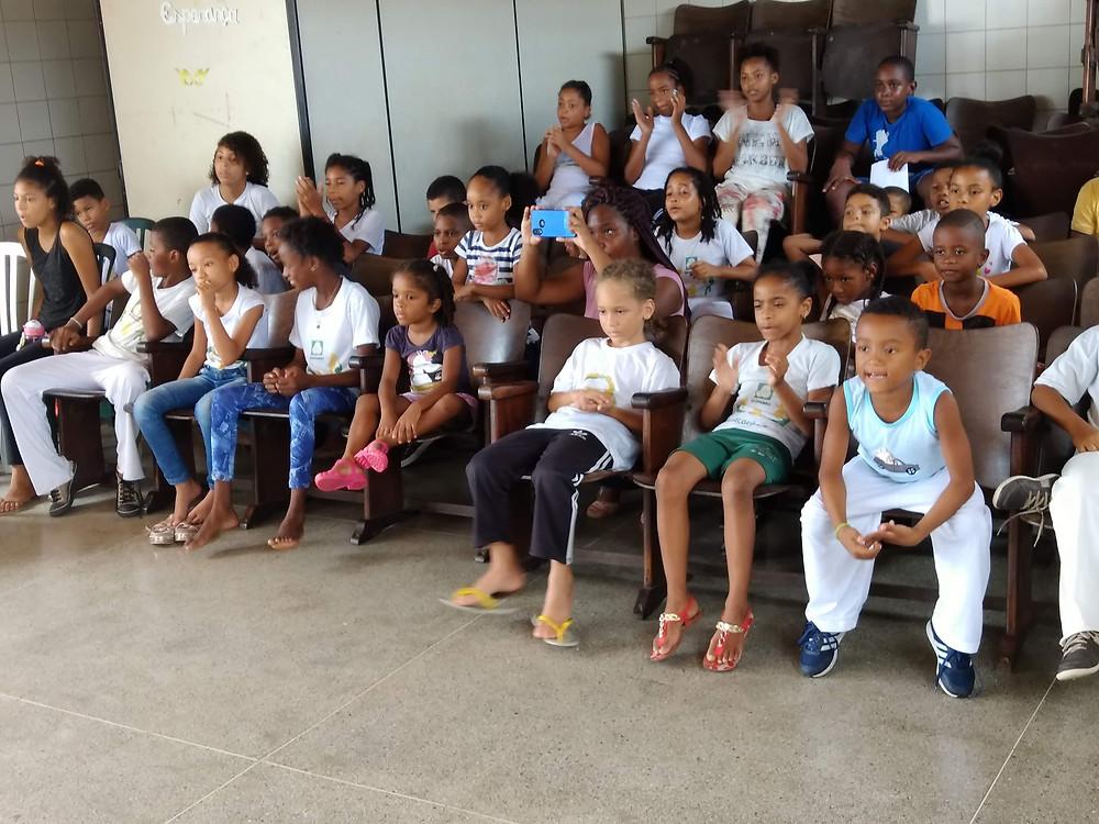 Crianças assistem atentas apresentação de capoeira