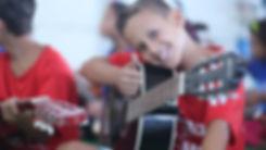Menino sorrindo segurando um violão