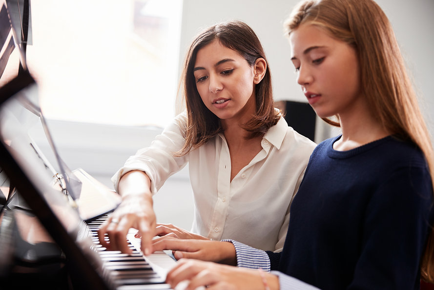 Female Pupil With Teacher Playing Piano