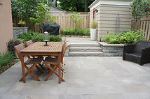 Outdoor living space with stone patio, dining area and outdoor storage.