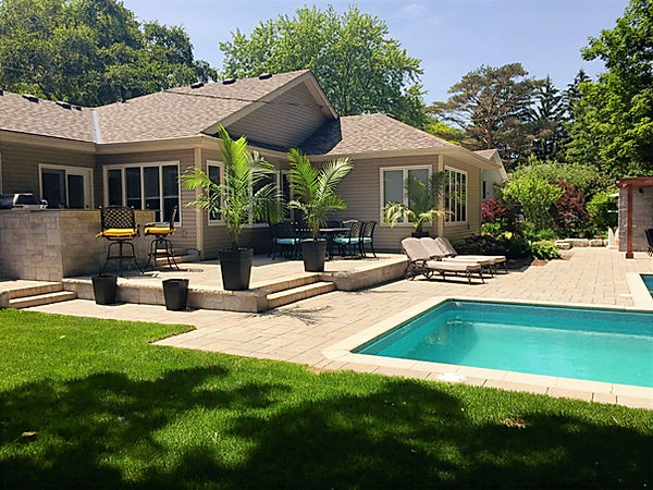 Large patio with outdoor kitchen and dining area, pool