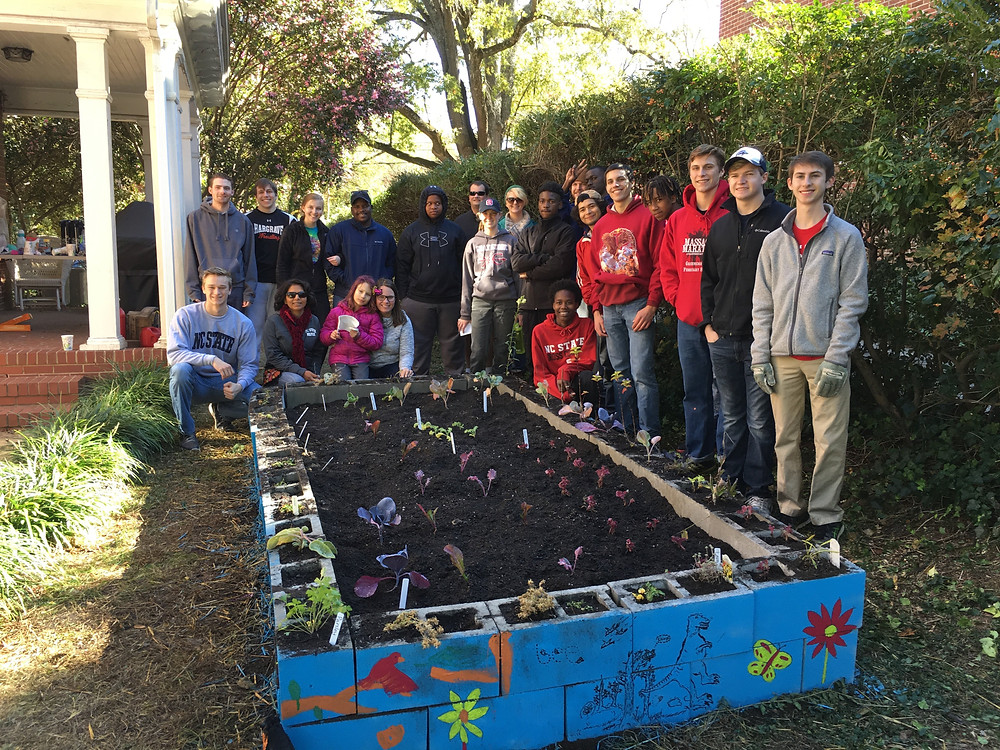 The volunteers, mentor, student leader, and family all in one picture with the finished garden!