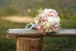 The wedding bouquet lies on a bench. Wed