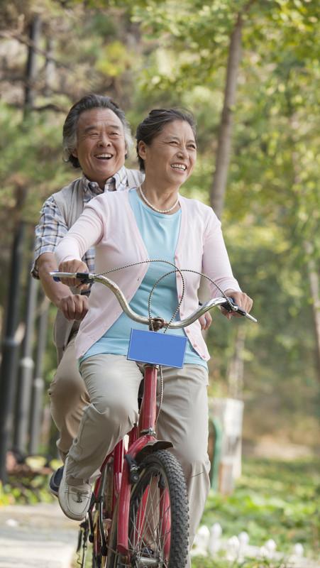 Older couple riding tandem bicycle, Beij