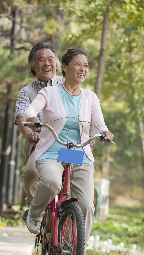 Older couple riding tandem bicycle, Beij