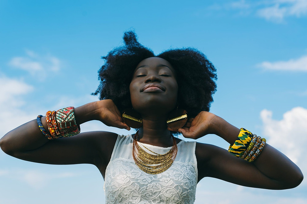 Black woman posing with a smile on her face, natural hair