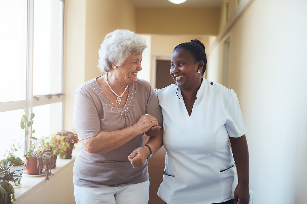 Portrait of smiling home caregiver and senior woman walking together through a corridor. H